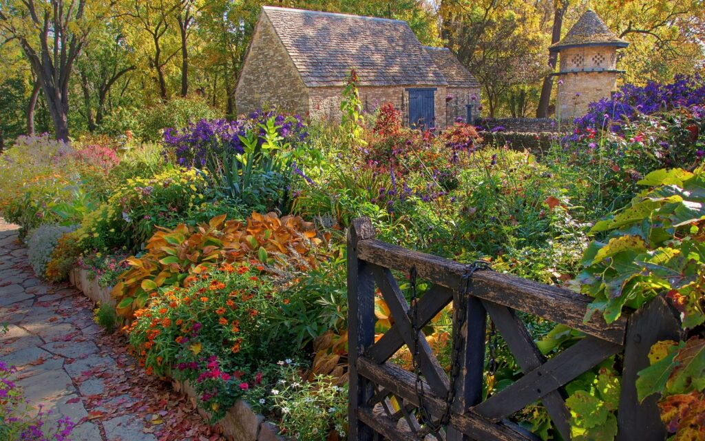 Michigan State University Salary Cuts. Fall scene with stone cottage, walkway and fence
